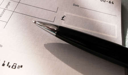 bank records: A blank pound sterling cheque and a biro pen.