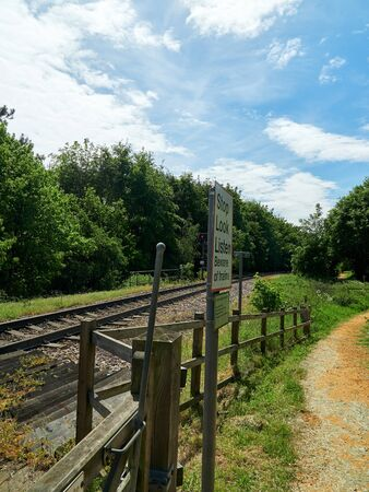 View towards Northern Rail Terminal at foot crossing with Stop Look Listen sign.