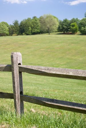 Wood Split Rail Fence with Grassy Landscape Background photo