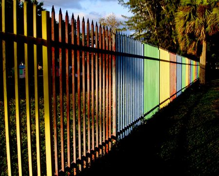 schoolyard: Yellow red blue green playground fence.