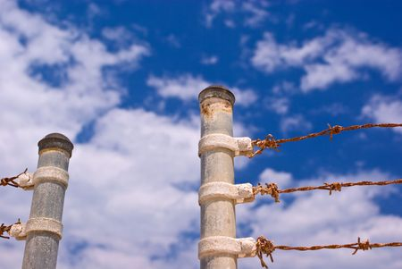 Sunbaked Metal Gate Posts and Rusty Barbed Wire Fence Against Partly Cloudy Blue Sky
