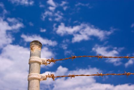 fenced in: Sunbaked Metal Gate Posts and Rusty Barbed Wire Fence Against Partly Cloudy Blue Sky  Stock Photo