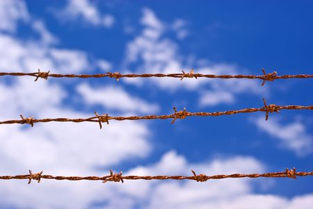 Three Strands of Sunbaked Barbed Wire Against Partly Cloudy Blue Sky