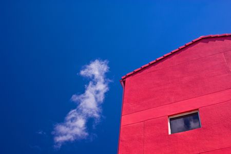Red Building With One Window Against Partly Cloudy Blue Sky