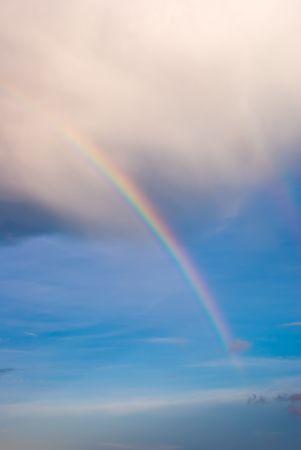 Double Rainbow Extending Below Base of Clouds in Blue Sky