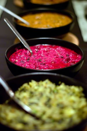 A row of bowls of colorful Indian food on a table.