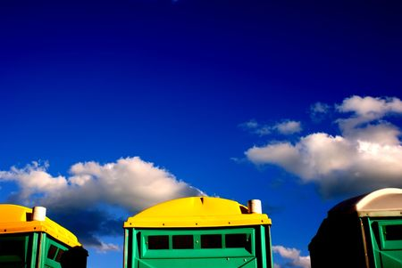 Portable toilets lined up against deep-blue sky. Stok Fotoğraf