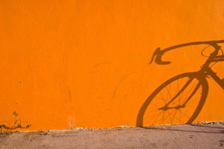 Bicycle Shadow on Orange Wall