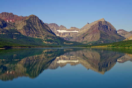 The mountains reflecting in a calm lake on a sunny summer day.