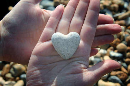 heart of stone: Heart shaped stone in palm of hand Stock Photo