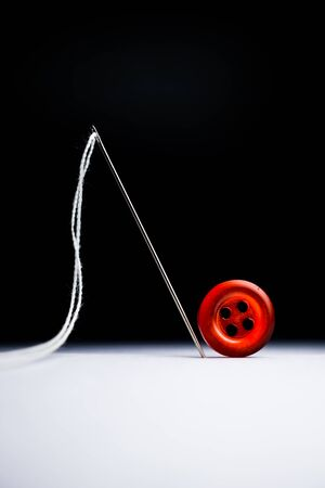 thread needle and red button isolated vertical Standard-Bild
