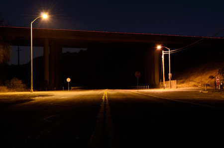off ramp: A night view of an intersection, near a bridge