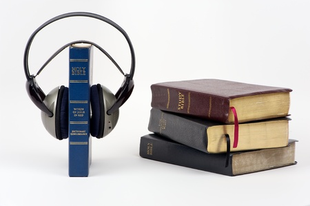 listen to music: Blue Bible with audio headphone and stack of bible on isolated white background