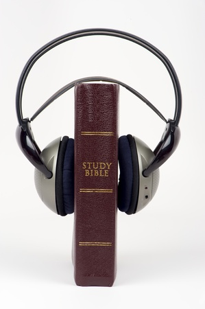 Red Bible with audio headphone on isolated white background photo