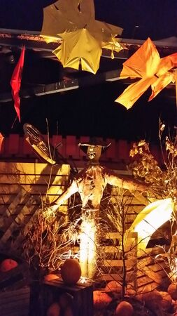 a scarecrow among pumpkins during halloween night
