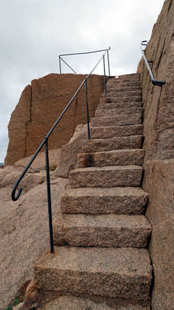 A granite staircase with an iron balustrade on an autumn afternoon