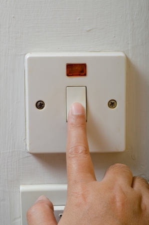 Finger turning white light switch on or off photo
