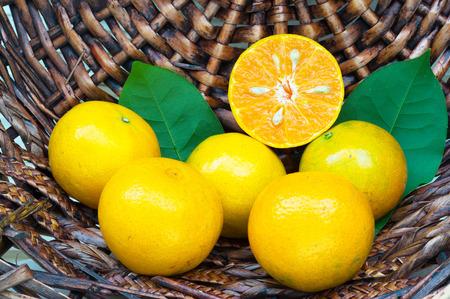 half  cut: full and half cut of fresh orange on the basket