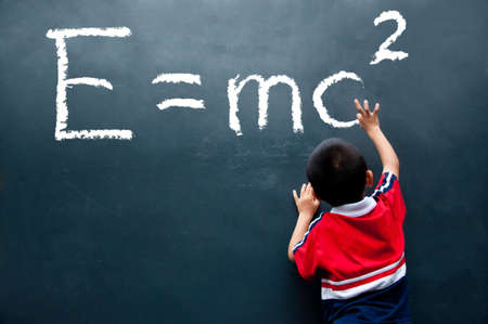 boy drawing E=mc2 on the wall photo