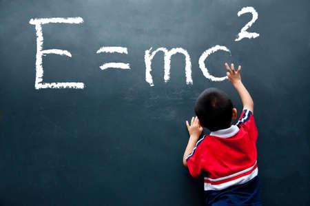 einstein: boy drawing E=mc2 on the wall