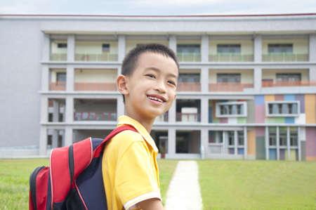 ir al colegio: Chico asi�tico feliz de ir a la escuela Foto de archivo