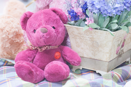 pink teddy bear: Cute pink teddy bear and fake flower on loincloth pattern background