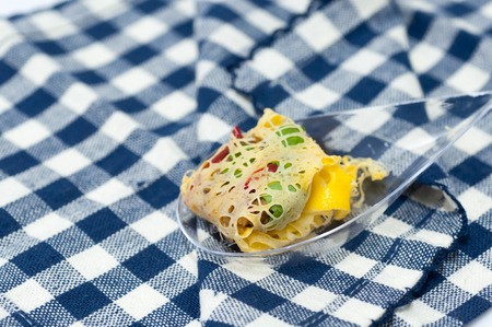 phuket food: Thai snack food named Rhoom or La-tiang (Minced Pork and Shrimp wrapped in Egg-net) on fabric pattern background Stock Photo