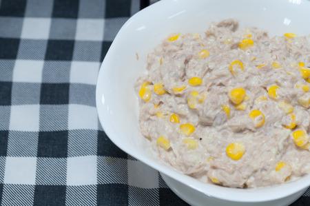 tuna mayo: Tuna corn salad cream in white bowl on fabric pattern background Stock Photo