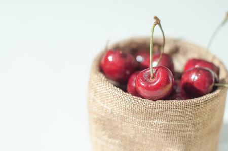 jute sack: Sweet cherries in jute sack on isolated white background Archivio Fotografico
