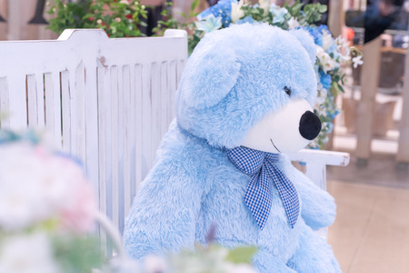 Big blue bear doll sit on the chair