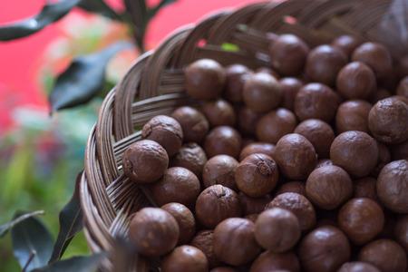 Macadamia nuts on scoop on Wicker basket, seletive focus Stock Photo