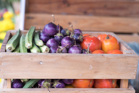Purple eggplant and okra in a wooden crate Stock Photo