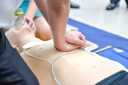 compressions: Basic Life Support of Demonstrating chest compressions on CPR doll Stock Photo