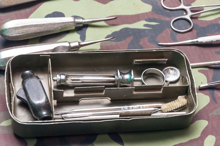오래 된 스테인레스 스틸 상자 군사 위장 배경에 오래 된 치과 도구