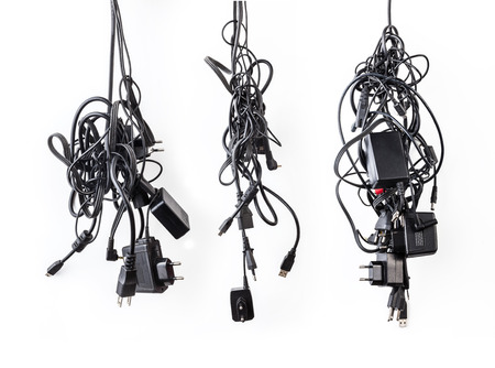 Cluster of messy chaotic power cables and adapters isolated on white background photo
