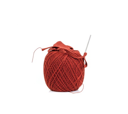 brown thread ball and needle with red thread isolated on white photo