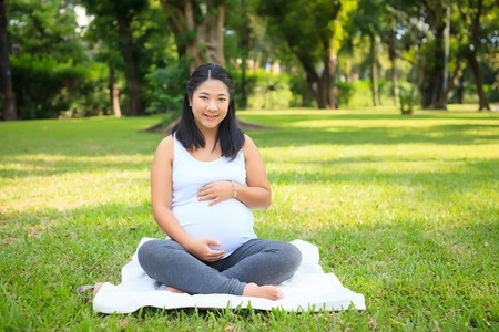 asian pregnant: Beautiful pregnant asian woman relaxing in the park