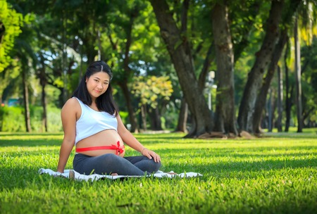 Beautiful pregnant asian woman relaxing in the park with red ribbon photo