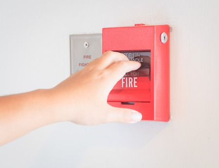 fire safety: The hand  is pulling fire alarm on the wall