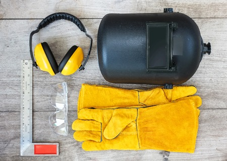 ear muffs: set of tools on wooden board, ear muffs,angle grinder,leather gloves