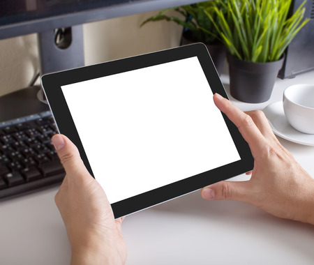 hands of a man holding blank tablet device over a workspace table Stock Photo