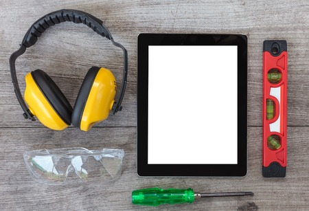 ear muffs: Top View of Digital Tablet and Assorted tools on wooden board, ear muffs,angle grinder,leather gloves Stock Photo