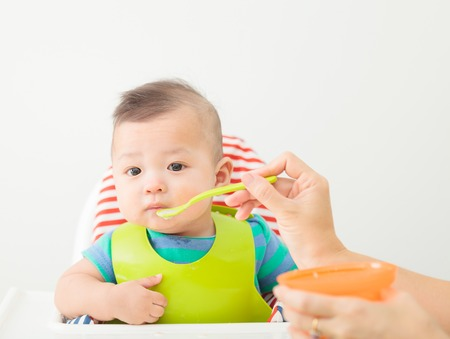 baby child eating in chair Imagens
