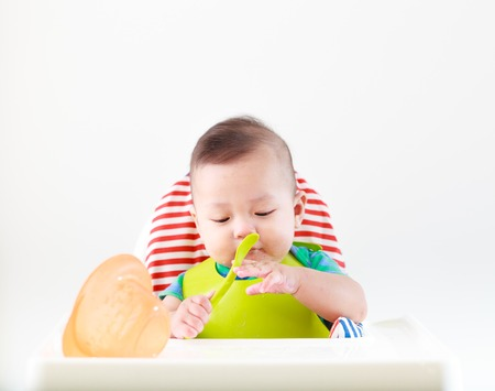 baby with spoon: baby child eating in chair Stock Photo