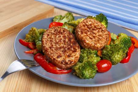 circular muscle: Two fried cutlets on a plate next to peppers and broccoli. Stock Photo