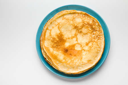 shrove tuesday: Golden pancakes on a blue plate. Traditional Russian dish on Shrove Tuesday Stock Photo