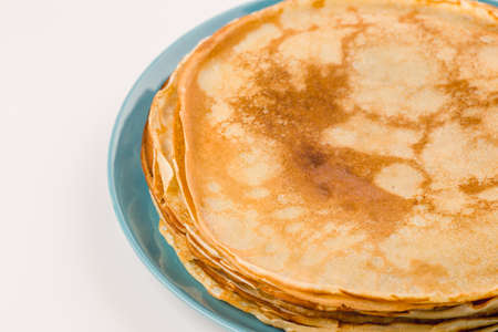 tuesday: Golden pancakes on a blue plate. Traditional Russian dish on Shrove Tuesday Stock Photo