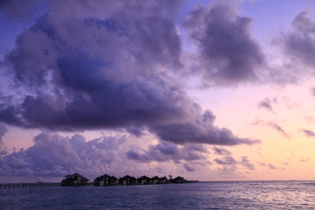 A row of water villas at Gili Lankanfushi (formerly Soneva Gili) against a purple sunset in the Maldives photo