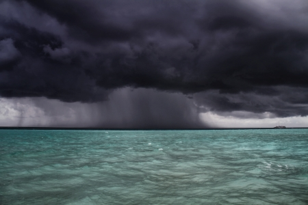 A dark storm and rain approaches a boat at Gili Lankanfushi (formerly Soneva Gili) in the Maldives photo