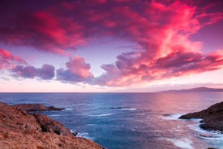 The sky lights up purple and pink looking out to sea from Ile Rousse over Cap Corse in Corsica Stock Photo